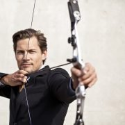 Businessman focusing on his target using a bow and arrow