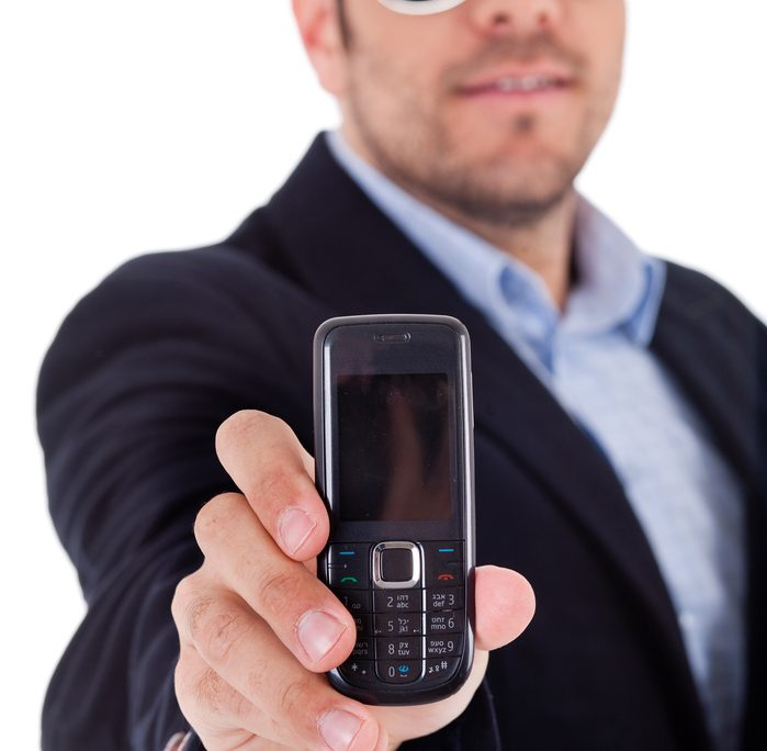 A business man holding the most indestructible object known to humanity - the Nokia phone
